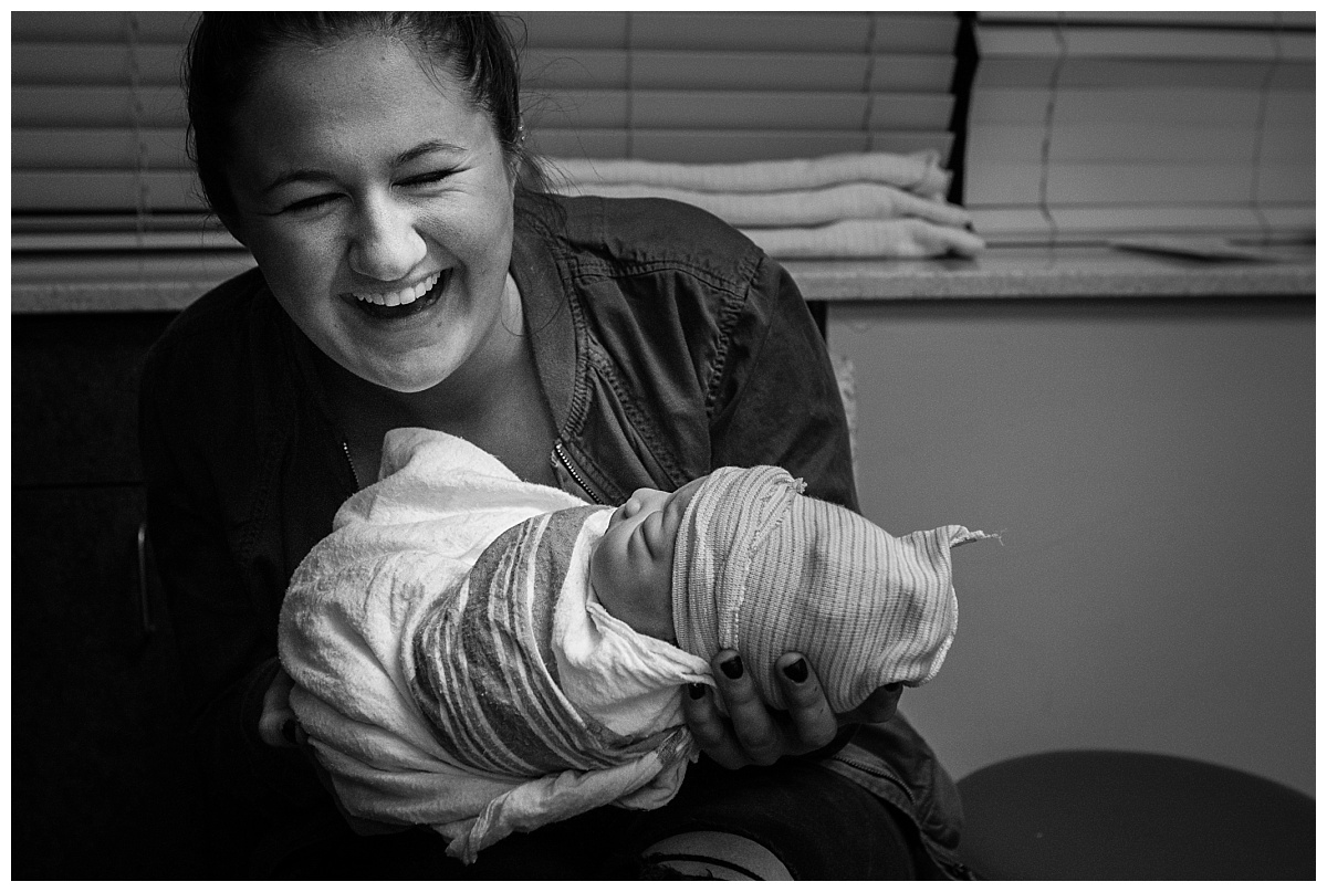 young woman holding newborn baby at the hospital